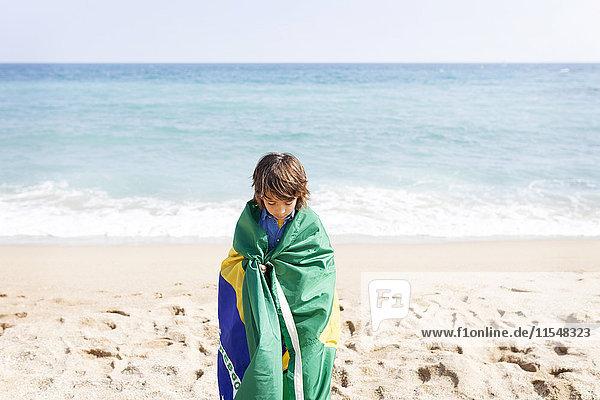 Kleiner Junge in brasilianischer Flagge am Strand gewickelt