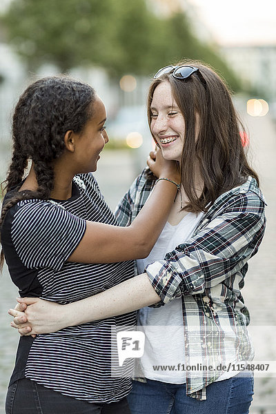 Two happy teenage girls hugging outdoors