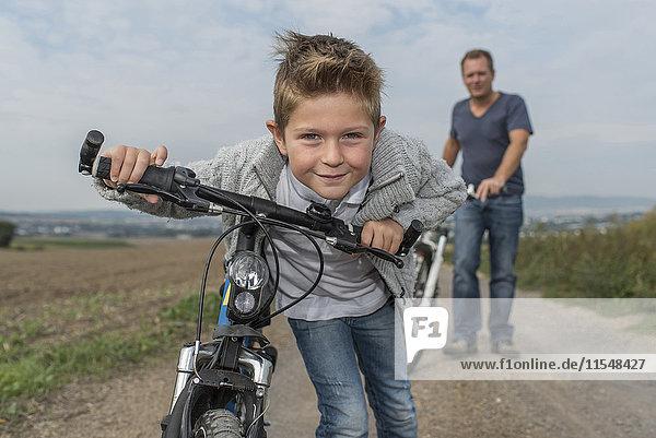 Portrait des kleinen Jungen auf Fahrradtour mit seinem Vater im Hintergrund