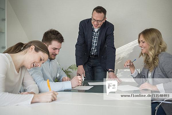Vier lächelnde Kollegen bei einer Besprechung auf Papier