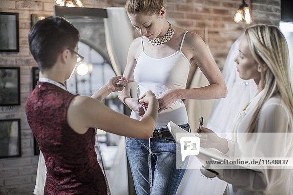 Wedding dress designer working  bride to be  measuring hip measurement