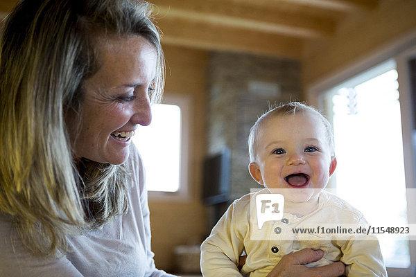 Porträt eines lachenden Jungen  der von seiner Mutter gehalten wird.