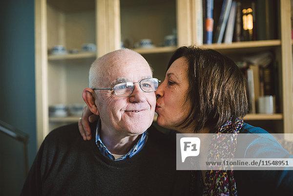 Seniorin  die ihren Mann zu Hause küsst.