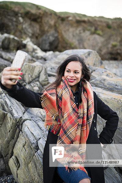 Spanien  Ferrol  Porträt einer lächelnden Frau  die einen Selfie mit ihrem Smartphone vor Felsen nimmt.