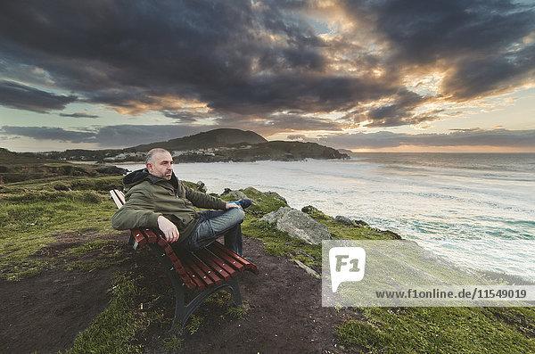 Spanien  Ferrol  Mann sitzt auf einer Bank an der Küste und schaut in die Ferne.