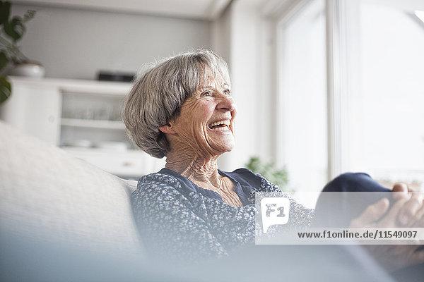 Porträt einer lachenden Seniorin,  die zu Hause auf der Couch sitzt.