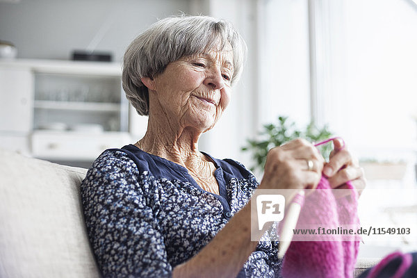 Porträt der strickenden Seniorin  die zu Hause auf der Couch sitzt.