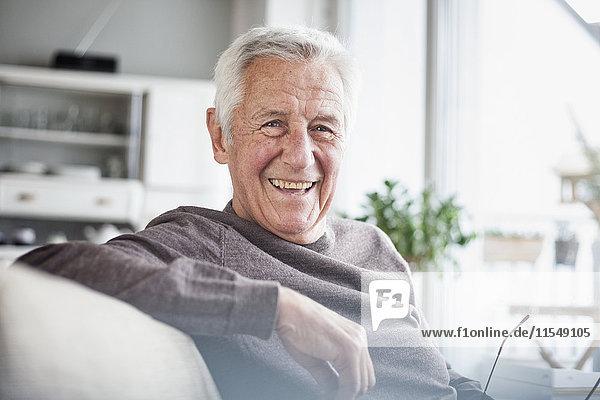 Porträt eines glücklichen älteren Mannes  der zu Hause auf der Couch sitzt.