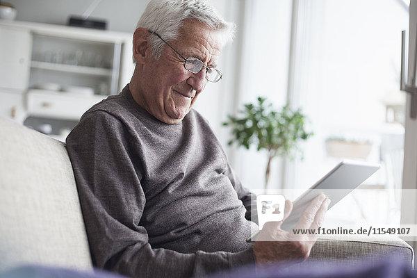 Porträt eines älteren Mannes  der zu Hause auf der Couch sitzt und ein digitales Tablett benutzt.