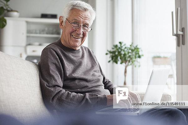 Porträt eines lächelnden älteren Mannes  der zu Hause auf der Couch sitzt und einen Laptop benutzt.
