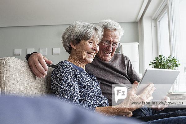 Glückliches Seniorenpaar sitzt auf der Couch im Wohnzimmer mit digitalem Tablett