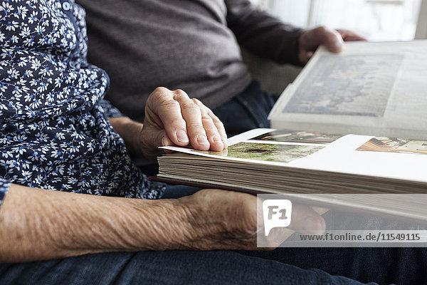 Hände des älteren Paares mit Fotoalbum  Nahaufnahme