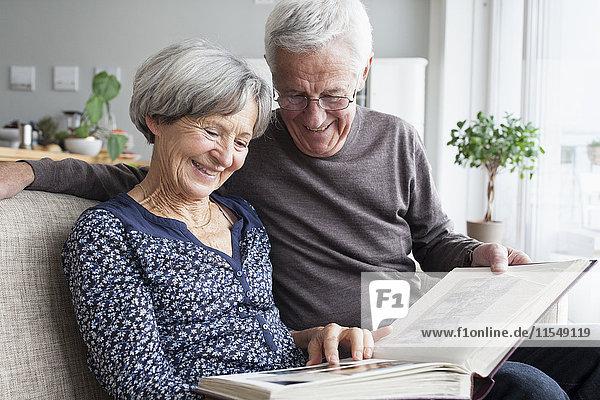 Glückliches älteres Paar  das auf der Couch des Wohnzimmers sitzt und sich ein Fotoalbum ansieht.