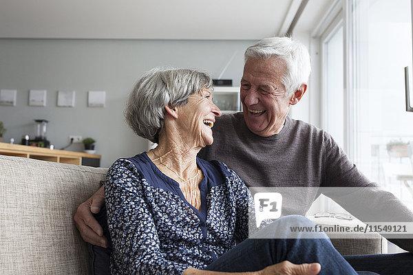 Lachendes Seniorenpaar  das zusammen auf der Couch im Wohnzimmer sitzt.