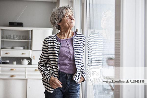 Porträt einer älteren Frau  die zu Hause durchs Fenster schaut.