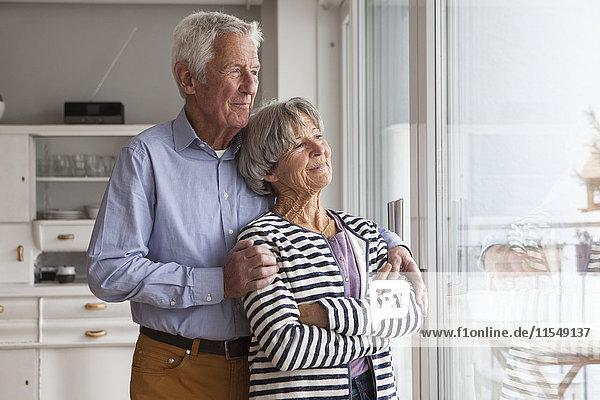 Porträt eines selbstbewussten Seniorenpaares beim Blick durchs Fenster zu Hause