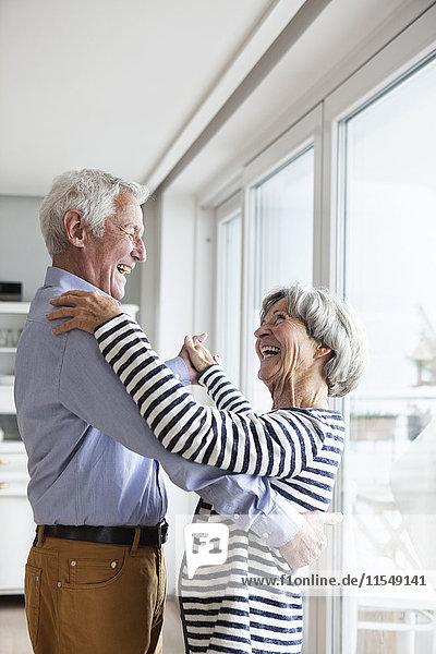 Seniorenpaar tanzt zu Hause zusammen.