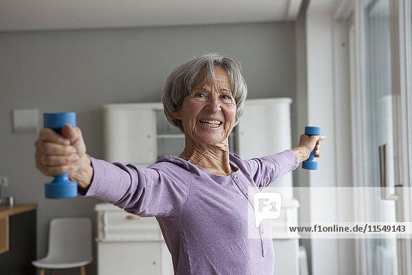 Porträt einer glücklichen Seniorin beim Fitnesstraining mit Hanteln zu Hause
