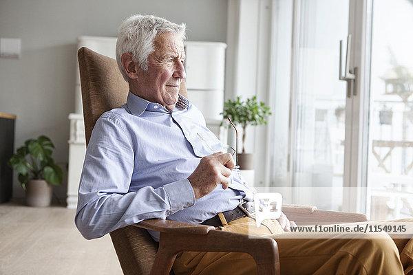 Porträt eines älteren Mannes  der zu Hause auf einem Sessel sitzt und durchs Fenster schaut.