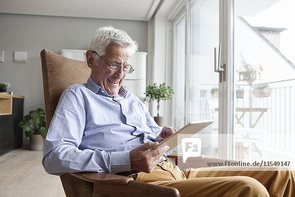 Porträt eines glücklichen älteren Mannes  der zu Hause auf einem Sessel sitzt und ein digitales Tablett benutzt.