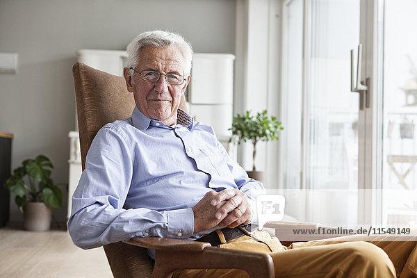 Porträt eines lächelnden älteren Mannes  der zu Hause auf einem Sessel sitzt.