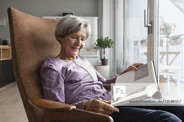Porträt einer älteren Frau  die zu Hause auf einem Sessel sitzt und ein Fotoalbum anschaut.