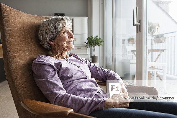 Porträt einer älteren Frau  die zu Hause auf einem Sessel sitzt und durchs Fenster schaut.