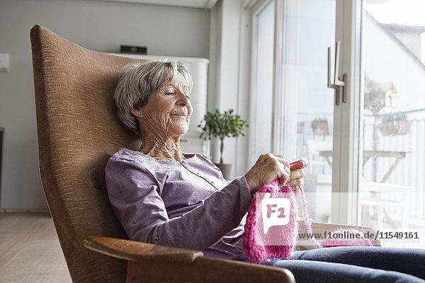 Porträt einer älteren Frau  die zu Hause auf einem Sessel sitzt und strickt.