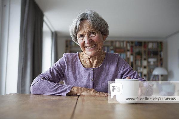 Porträt einer älteren Frau  die bei einer Tasse Kaffee am Tisch sitzt.