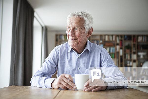 Porträt eines nachdenklichen älteren Mannes  der bei einer Tasse Kaffee am Tisch sitzt und durchs Fenster schaut.