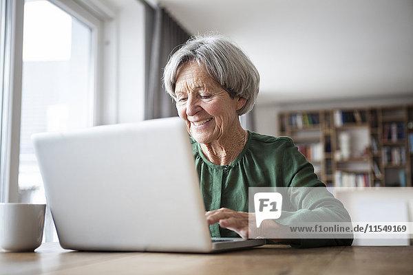 Porträt einer älteren Frau mit Laptop zu Hause