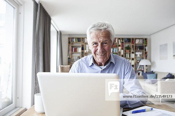 Portrait eines älteren Mannes am Tisch im Wohnzimmer mit Laptop
