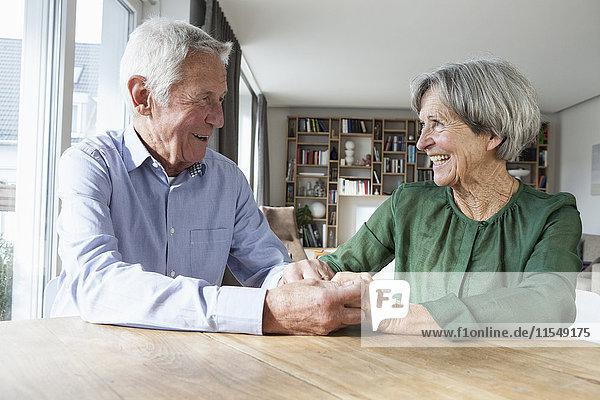 Ein glückliches Ehepaar,  das zu Hause Händchen hält.