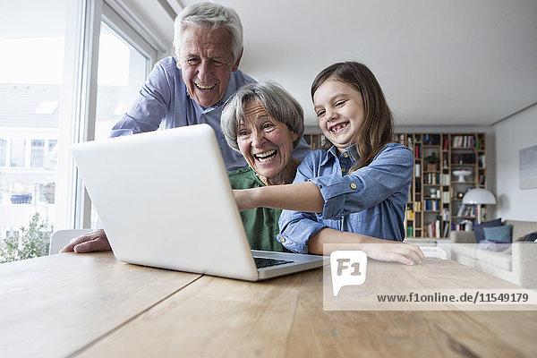 Die Großeltern und ihre Enkelin haben Spaß mit dem Laptop zu Hause.