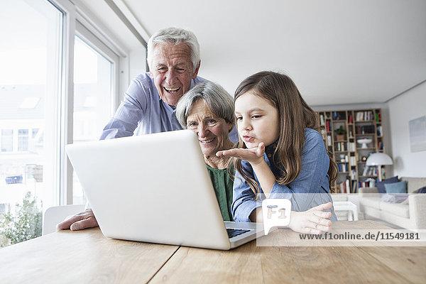 Großeltern und ihre Enkelin skyping mit Laptop zu Hause