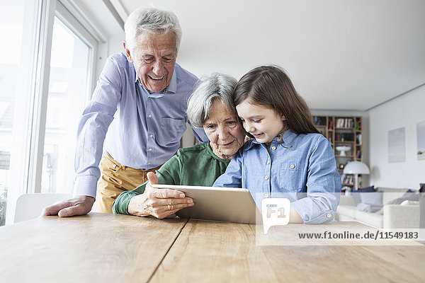 Großeltern und ihre Enkelin beim Betrachten des digitalen Tabletts zu Hause