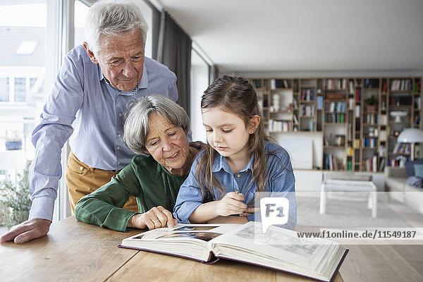 Großeltern beim Betrachten des Fotoalbums mit ihrer Enkelin zu Hause