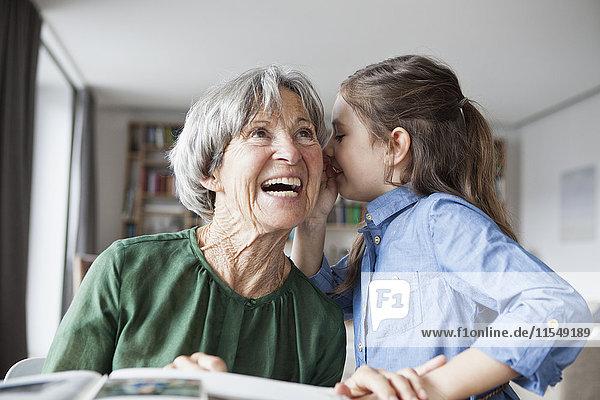 Enkelin flüstert ihrer Großmutter etwas ins Ohr.