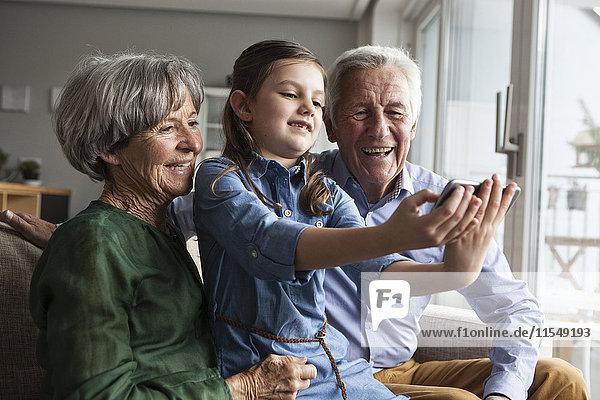 Kleines Mädchen nimmt Selfie mit ihren Großeltern mit nach Hause