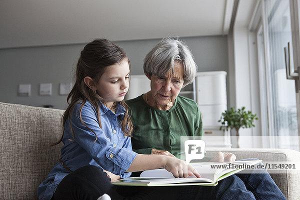 Großmutter und ihre Enkelin sitzen zusammen auf der Couch mit einem Buch.