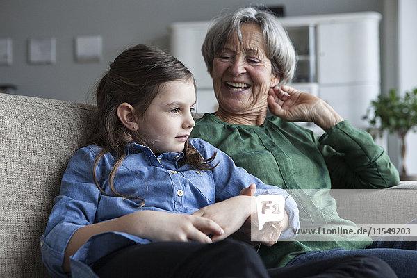 Großmutter und ihre Enkelin sitzen zusammen auf der Couch zu Hause.