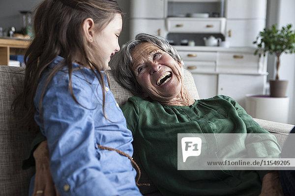 Lachende Großmutter und ihre Enkelin auf der Couch zu Hause