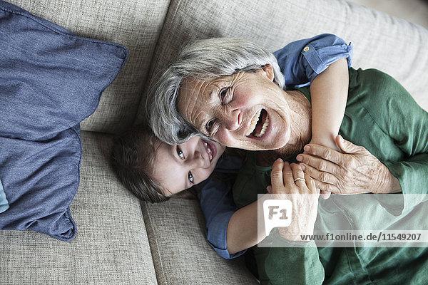 Porträt der lachenden Großmutter und ihrer Enkelin auf der Couch