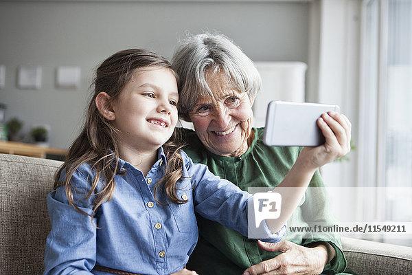 Großmutter und ihre Enkelin sitzen zusammen auf der Couch und nehmen Selfie mit Smartphone.