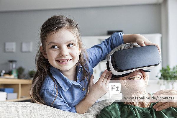 Seniorin und ihre Enkelin haben Spaß mit der Virtual Reality Brille zu Hause.