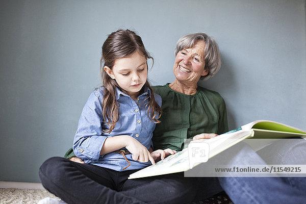 Glückliche Großmutter und ihre Enkelin sitzen mit einem Buch auf dem Boden.