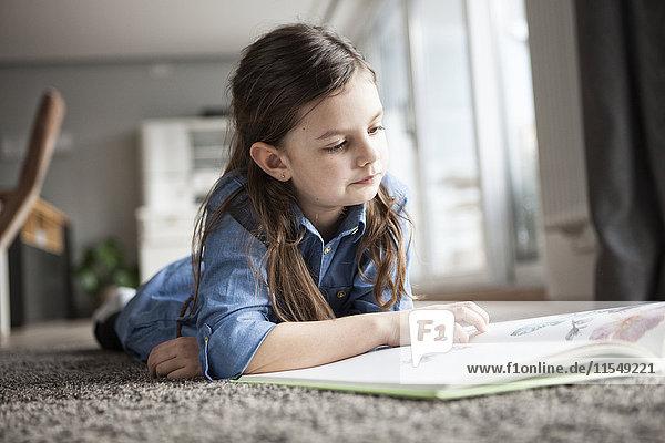 Porträt eines kleinen Mädchens  das auf dem Boden liegt und sich ein Bilderbuch ansieht.