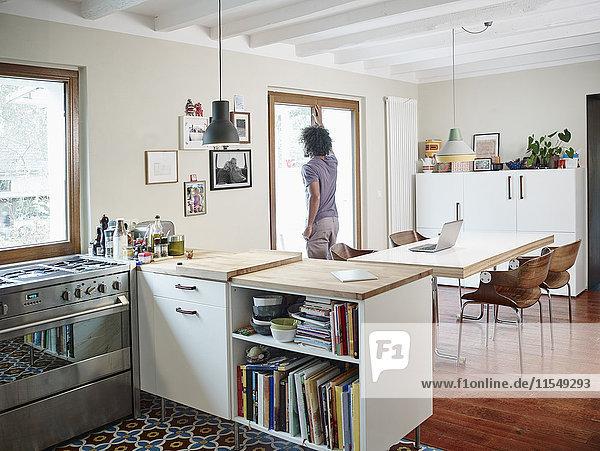 Junger Mann mit Blick aus dem Fenster in der offenen Küche