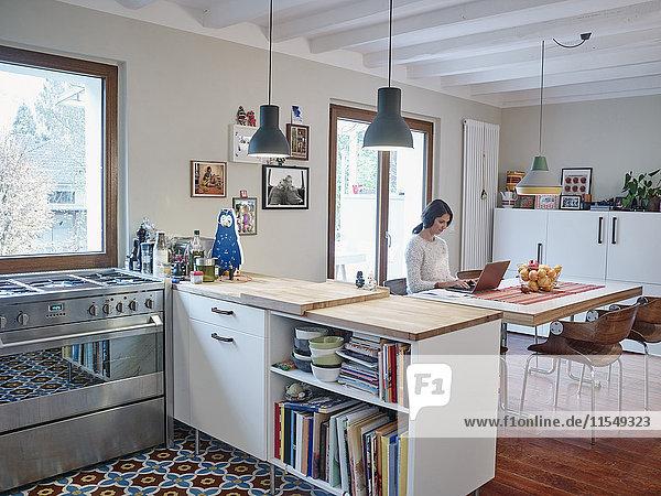 Woman using laptop in open plan kitchen