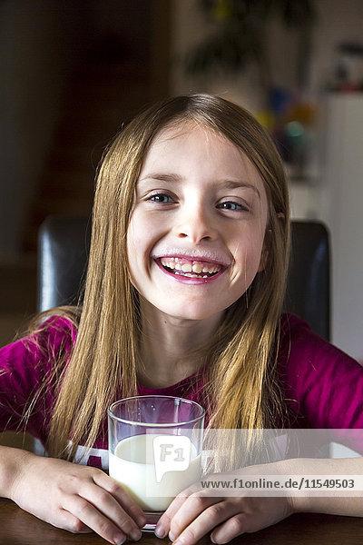 Portrait of happy girl with glass of milk